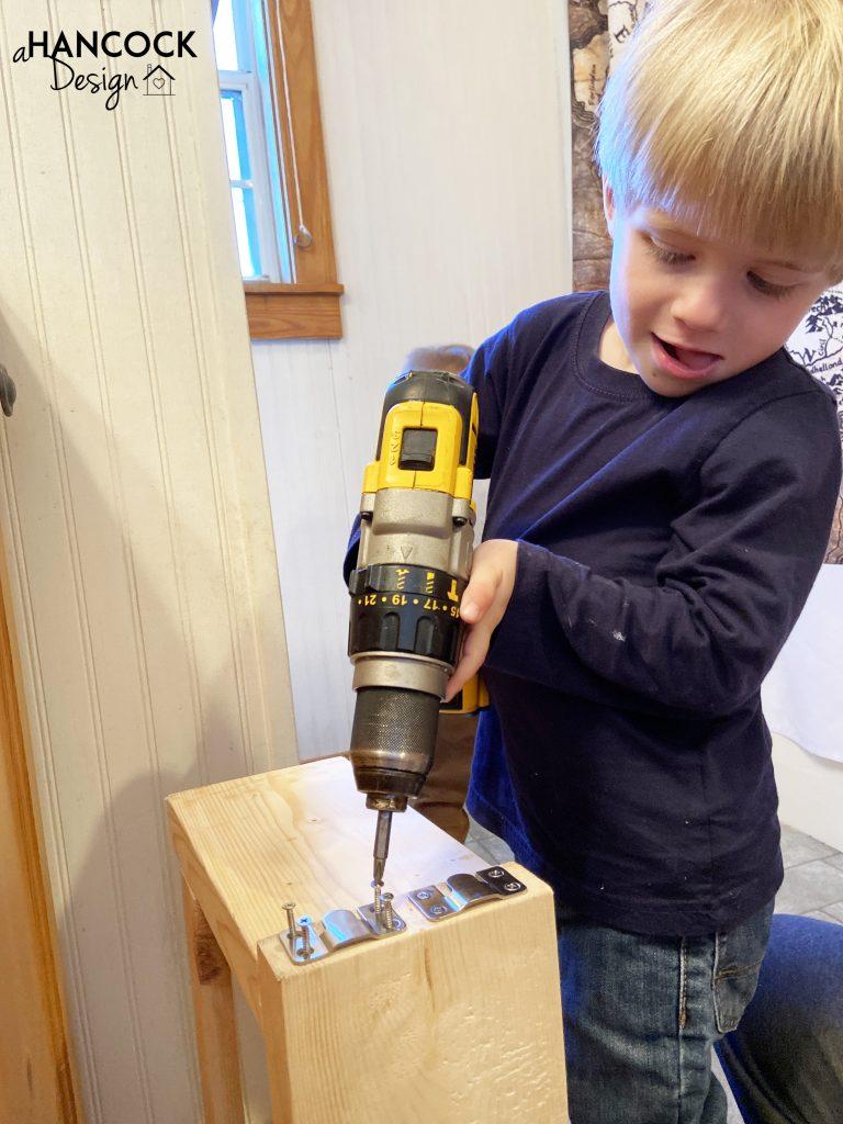 little boy using drill