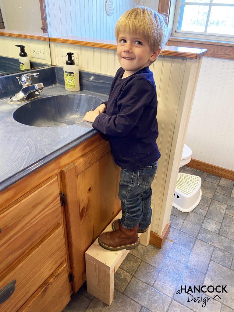 little boy standing on bathroom stool